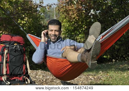 Happy Hispanic traveler having a conversation on mobile phone while laying in a hammock on vacation