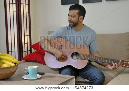 Hispanic male musician relaxing and playing classic guitar at home