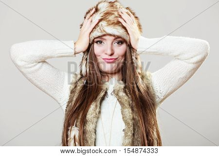Winter cute girl fashion. Smiling woman wearing sweater fur vest and warm hat in freezing cold time with hands on head.