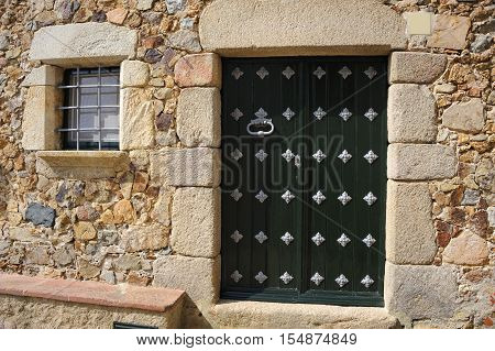 Entrance door of the old stone house, in the medieval walled town Tossa de Mar, Spain
