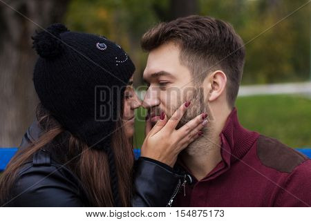 Closeup shot of young beautiful stylish couple in autumn park. She is kissing him. He has a beard. She has a piercing in the nose. She wears black hat with bubo.