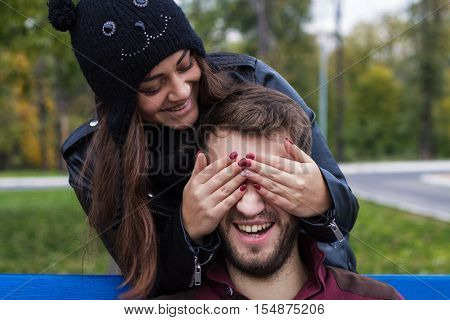 Closeup shot of young beautiful laughing stylish couple in autumn park. They look happy. She is kissing him. He has a beard. She has a piercing in the nose. She wears black hat with bubo.