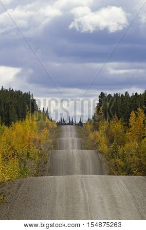 Autumn along the adventurous rise and fall of Cassiar-Stewart Highway in British Columbia. Vertical photograph with copy space in sky. Rambling road travel symbol. Date is September 6 2015.