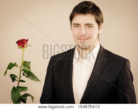 Relationship boyfriend on date. Handsome man with rose good looking male with beautiful red flower for his love.
