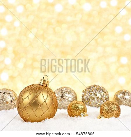 Golden Christmas Ornaments In Snow With Twinkling Gold Background