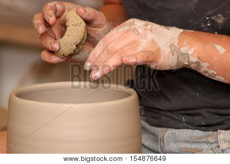 In the pottery studio: A potter's hands shape a pot using a sponge