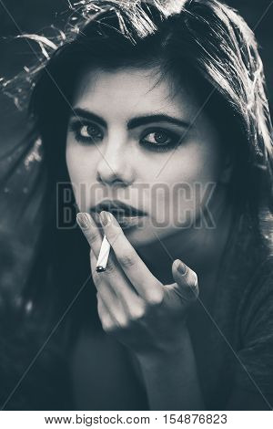 Closeup black and white portrait of white Caucasian beautiful young woman lying on ground grass smoking cigarette bad unhealthy habit lifestyle concept