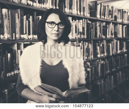 Black and white retro vintage toned portrait of middle age mature Caucasian woman student with glasses in library holding book looking in camera teacher librarian back to school