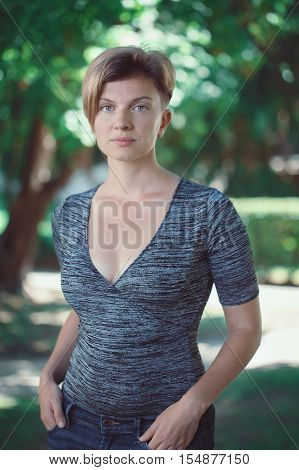 Portrait of sad pensive young middle aged white caucasian girl woman with short hair stylish haircut in tshirt looking in camera outside in summer park beauty fashion lifestyle