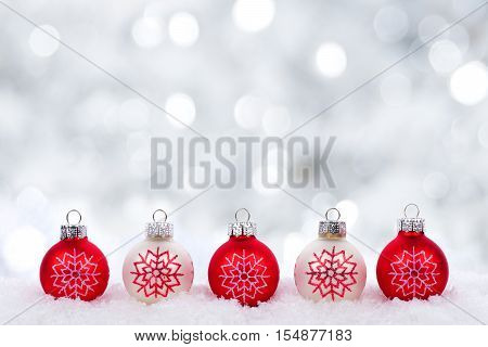 Red And White Christmas Ornaments With Snowflakes In Snow With Twinkling Silver Background