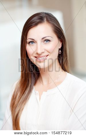 Closeup portrait of beautiful smiling nice young white Caucasian business woman with blue eyes long blond hair wearing white office blouse shirt looking in camera slavic Russian face