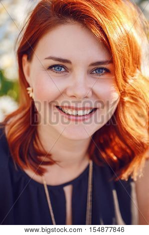 Closeup portrait of smiling middle aged white caucasian woman with waved curly red hair in black dress looking in camera outside in park garden beauty fashion lifestyle concept