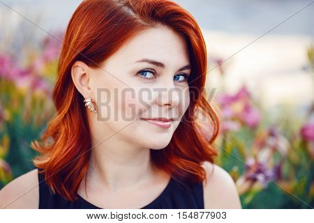 Closeup portrait of smiling middle aged white caucasian woman with waved curly red hair in black dress looking in camera outside in park among flowers beauty fashion lifestyle concept