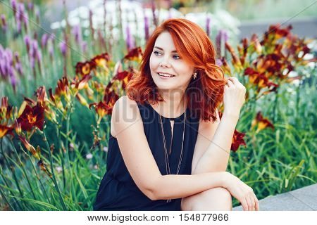 Closeup portrait of smiling middle aged white caucasian woman with waved curly red hair in black dress looking away outside in park garden among flowers beauty fashion lifestyle concept