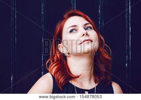 Closeup portrait of smiling middle aged white caucasian woman with waved curly red hair in black dress looking away dreaming on black background beauty fashion lifestyle concept