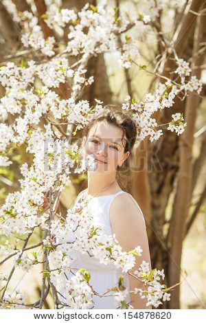 Closeup portrait of beautiful sexy Caucasian adult girl woman with dark brown hair and hazel eyes in white dress looking in camera among blooming trees sakura flowers in spring summer