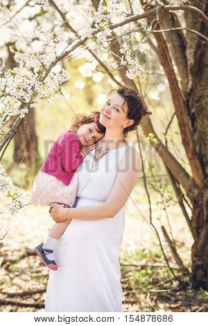 Portrait of caucasian pregnant mother in long white open dress holding her daughter in pink clothes on a spring summer day in the park outside among blooming cherry trees