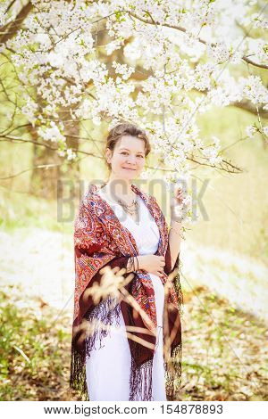 Portrait of pregnant caucasian young girl woman in white dress with colorful ethnic shawl scarf standing in park outside on sunny spring summer day