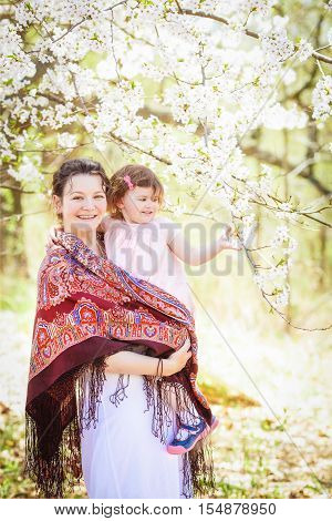 Portrait of caucasian pregnant mother in white dress and shawl scarf with ethnic folk motifs pattern decoration holding her daughter in pink clothes on spring summer day in park outside among blooming cherry trees