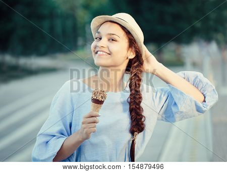 Closeup portrait of beautiful happy white Caucasian brunette girl woman with dimples on cheeks and tanned skin in blue dress and hat eating ice cream cone sunset on summer day lifestyle concept
