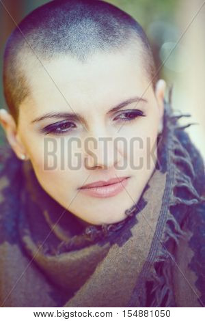 Closeup portrait of sad beautiful Caucasian white young bald girl woman with shaved hair head in leather jacket and scarf shaw looking away toned with Instagram filters in blue color