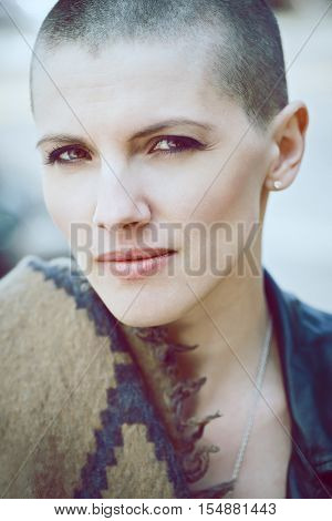 Closeup portrait of sad beautiful Caucasian white young bald girl woman with shaved hair head in leather jacket and scarf shawl looking in camera toned with Instagram filters in blue color