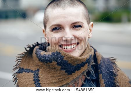 Closeup portrait of happy smiling laughing beautiful Caucasian white young bald girl woman with shaved hair head in leather jacket and scarf shawl looking in camera