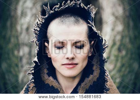 Closeup portrait of beautiful Caucasian white young bald girl woman with shaved hair head with closed eyes her head covered with scarf shawl spiritual mood state of mind
