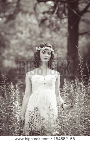 Black and white portrait of beautiful white Caucasian girl with long wavy curly hair and flowers chaplet on head. Attractive young woman model in park outside country village hippie style