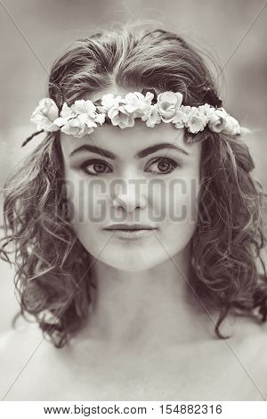 Black and white close-up portrait of beautiful white Caucasian girl with long wavy curly hair and flowers chaplet on head. Attractive young woman model in park outside country village hippie style