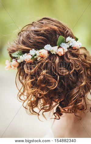 Closeup portrait of girl long wavy curly hair and flowers chaplet on head. Attractive young woman model in park outside country village hippie style no face hidden face bare shoulders