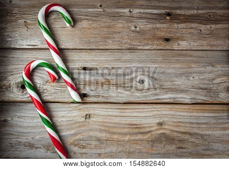horizontal image of an old rustic wood background with two large candy canes placed side by side on one side of the image great for a greeting card idea,