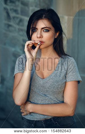 Portrait of white Caucasian beautiful young sexy brunette woman with light blue green eyes in jeans and t-shirt smoking cigarette looking in camera toned with filters lifestyle concept