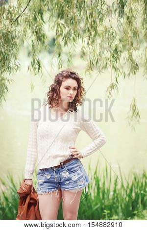 Portrait of beautiful Caucasian young girl woman with wavy curly hair in white sweater blue denim shorts and tall leather boots holding brown jacket posing outside in park summer autumn look