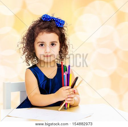 Cute little girl in blue dress, holds a lot of pencils . She paints at a table in a Montessori kindergarten.Winter brown abstract background with white snowflakes.