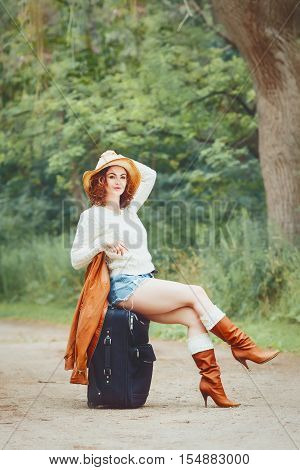 Portrait of a beautiful Caucasian young girl woman in white sweater high leather brown boots blue jeans shorts and straw hat sitting on travel back on the country road travel wonderlust adventure vacation concept