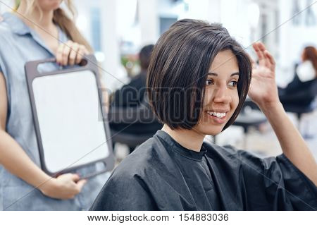 Closeup portrait of hispanic latin girl woman sitting in chair in hair salon looking in mirror at her new haircut short bob pixie happy joy emotion