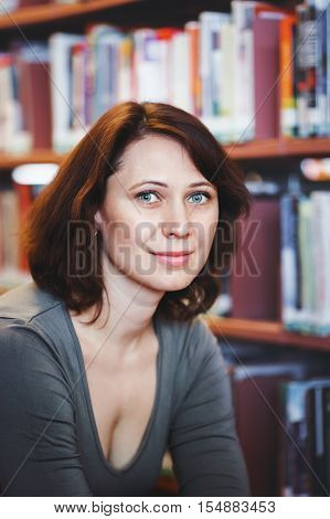 Closeup portrait of smiling middle age mature woman student in library looking in camera teacher librarian profession back to school concept