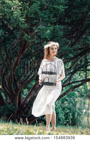 Portrait of beautiful smiling Caucasian young women girl in white long dress with flower chaplet holding empty birdcage in enchanted forest alone dreamy romantic gothic style