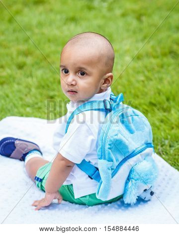 Portrait of cute adorable little indian mixed race infant boy in white shirt sitting on ground with blue backpack schoolbag in park field green grass outside back to school concept