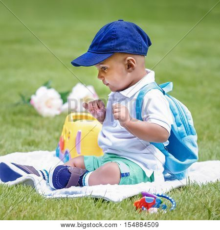 Portrait of cute adorable little indian mixed race infant boy in white shirt sitting on ground with blue backpack schoolbag and toys in park field green grass outside back to school concept