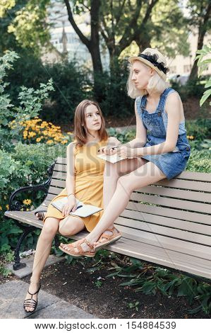 Portrait of two white Caucasian unformal young girls hipster students teenagers friends outside in park on summer day sitting on bench talking together drawing sketching best friends forever