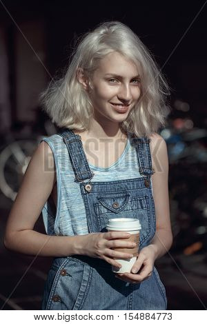Portrait of beautiful Caucasian teenage young blonde alternative model girl woman in blue tshirt jeans romper looking in camera holding cup of coffee toned with filters