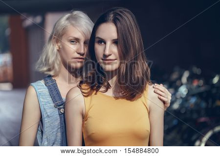 Portrait of two white Caucasian unformal young girls hipster students friends outside on summer day hugging together selective focus best friends forever