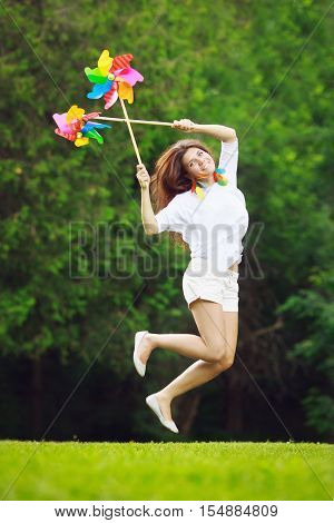 Portrait of a beautiful Caucasian young teen girl model with long hair in white shirt and pants holding windmill whizzer toys in her hands and jumping high in the air in happiness freedom and joy