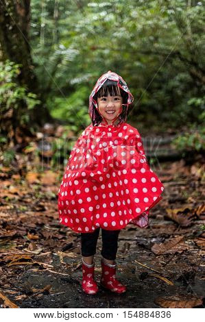 Happy Asian Chinese Little Girl Wearing Raincoat In Forest