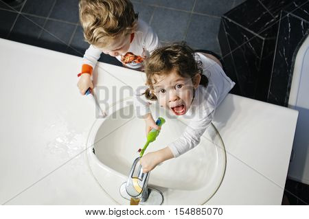 Closeup portrait of twins kids toddler boy girl in bathroom toilet washing face hands brushing teeth with toothbrash playing with water lifestyle home style everyday moments top view