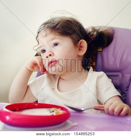 Portrait of cute bored Caucasian child kid girl sitting in high chair eating cereal with spoon early morning everyday lifestyle candid moments toned with filters
