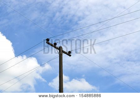 Electrical pole against hazy blue sky with power lines
