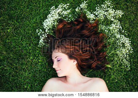 Closeup portrait of young beautiful girl woman with red brown hair lying on grass with white small flowers around her head. View from above top overhead. Concept of spring summer youth happiness
